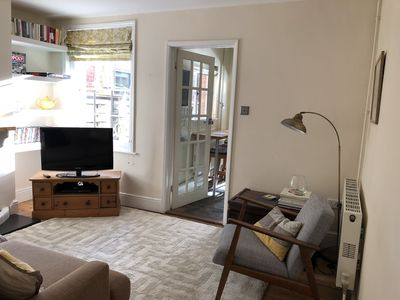 Sitting room with 3-seater sofa, stylish arm chair and wood burning stove