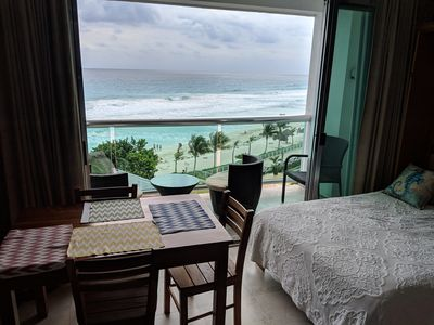 Oceanside room with table and double bed. Sit on deck with chairs and table