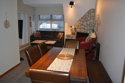 Living room with pullout couch and gas fireplace.  Table seats 7