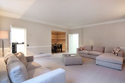 The very spacious Lounge and Dining Area featuring an original marble fireplace