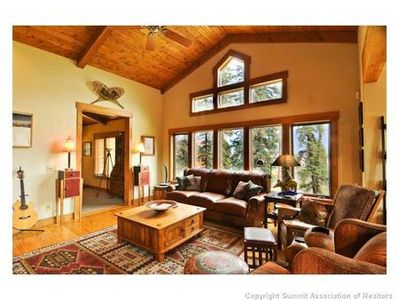 A true Colorado Rocky Mountain Great Room, with a wall of windows, soaring knotty pine ceilings and exposed beams. We even have skis over the fireplace!  Also enjoy the 50 inch flat screen LED TV.