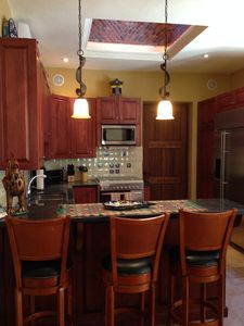Breakfast bar and fully equipped kitchen for cooking and baking.