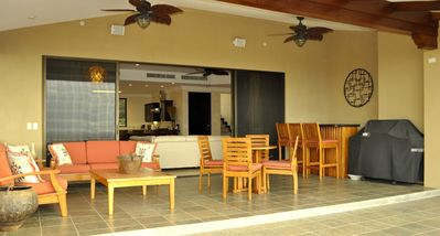 Ceiling Fans Over Outdoor Living Room With Dining Table Bar And Gas BBQ Grill