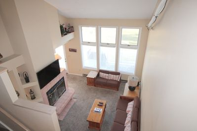 From loft down to main living area with wood burning fireplace.