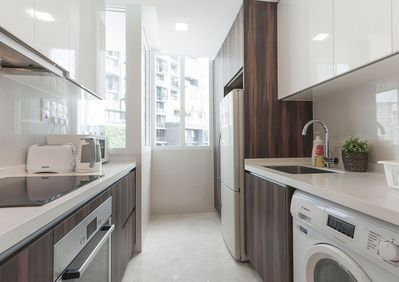 Modern well equipped kitchen with a view to lush greenery n adjacent newly completed condo .