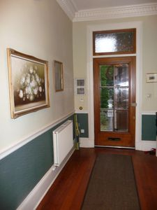 Welcoming front hallway with grand high Victorian ceilings