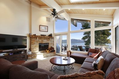 Living room with a huge flat screen tv, wood burning fire place, large sectional