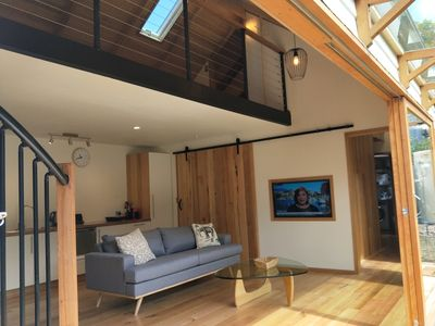 Open plan living/kitchen dining with wooden sliding doors onto outdoor area