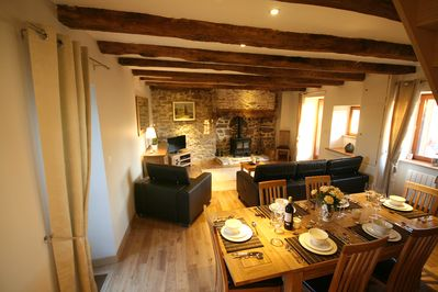Open plan lounge and dining area with TV and wood burning stove