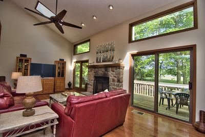 Main level living room with fireplace and deck with views of the lake