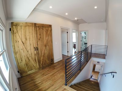 View of the stairway and the upstairs laundry, bedrooms, and bath