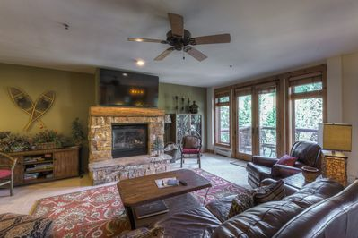 The living area features a flat screen TV above a gas fireplace and access to a large private balcony.