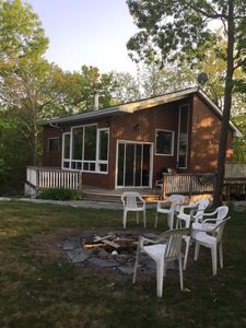 Cottage side view showing new landscaping, larger windows and doors and front deck with sunken hot tub overlooking the lake