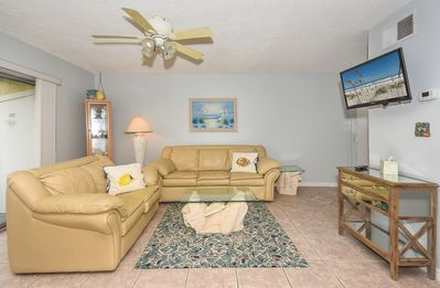 The living room features a leather love seat, full size sofa sleeper and flat screen TV.