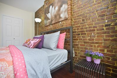 2nd Private bedroom with exposed brick wall and queen size bed