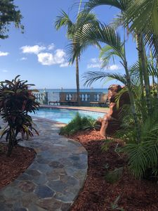 View from side yard to pool and beach beyond the wall.