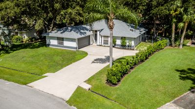 Aerial view of lush green lawn, privacy fence and oak trees.