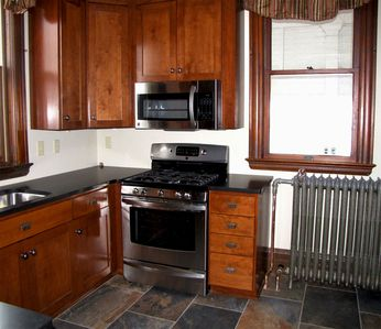 New kitchen with stainless steel appliances, slate floors & granite countertops