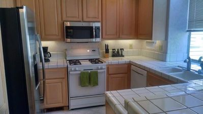 Fully-equipped kitchen with fridge, stove, microwave, coffee maker, etc.