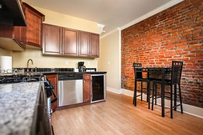 Walk into the middle level eat in kitchen with exposed brick and wine cooler!!