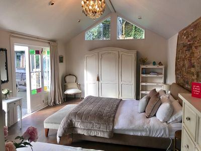 French inspired cottage bedroom leading onto pool and seating area