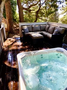 a decked hot tub and a grand oak and festive lighting