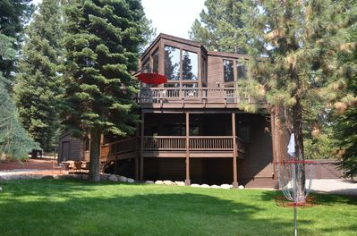 View of back decks, and grassy, fenced backyard.