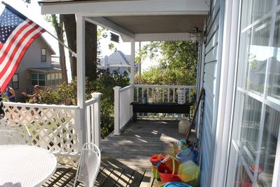 Front porch with a deck and umbrella for out door eating.