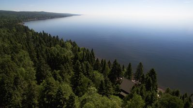 A drone image of the cottage wrapped in the forest with views of the lake.