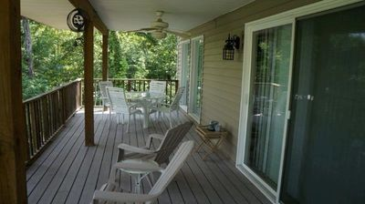 Huge covered deck great to relax rain or shine; fan and multiple tables