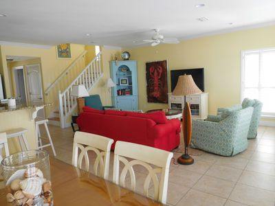 den w flat screen tv adjacent to kitchen and large deck overlooking sandy beach