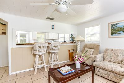 """Living Room - A colorful corner table in the living room holds baskets of shells, and our complimentary shell guide! A 50"""" TV, stereo, and games stock the entertainment center."""