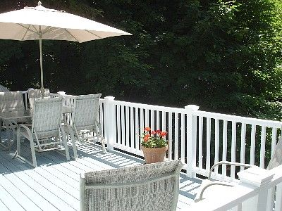 Beautiful sunny deck with bbq, plenty of seating, surrounded by beautiful trees