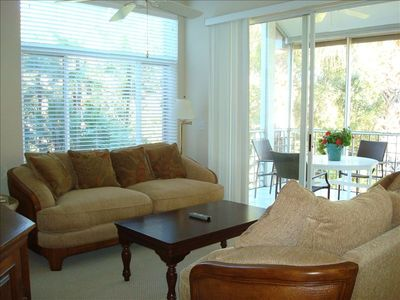 View of living room--high ceilings, fan, and lots of light/glass/fresh sea air!