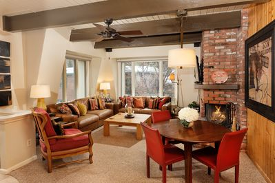 Cheerful living room with leather couches and a wood burning fireplace.