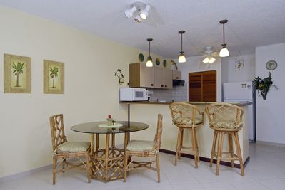 Dining area professional photo.  Table and bar area actually has 4 chairs and 4 stools.  Replaced tile floor is shown.