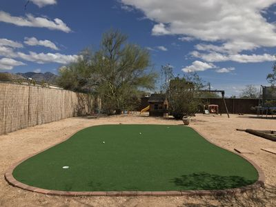 Huge putting green with putters and balls.