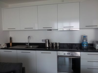 Kitchen area, with dishwasher and fridge freezer, and plates and utensils.