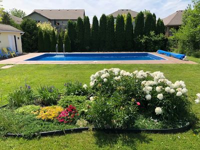 Large pool surrounded by colourful gardens