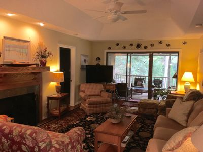 Spacious, open living room with plenty of seating and a flat screen TV