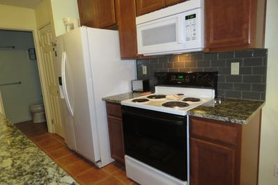 Upgraded kitchen with new refrigerator, granite counter, and back splash