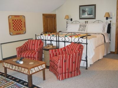 King sized bed with quality linens and chairs which face the lake and outdoors.