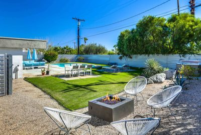 Exterior - Entertain in the large lush yard with a sparkling pool, hot tub, fire pit, and stylish outdoor furniture.