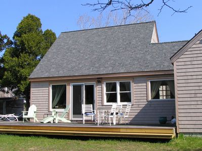 Back view of the house with the wrap around deck.  Adirondack and dining chairs.