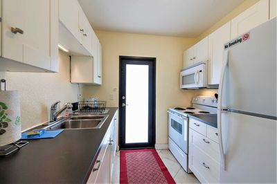 Fully equiped kitchen has full size fridge, range and built-in microwave.