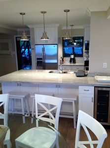 Designer kitchen with lots of seating, bar and a wine fridge.