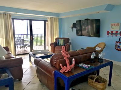 Family room with leather furniture and smart, flat, big screen TV.