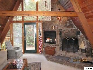 Mountain Stone fireplace surrounded by all wooden walls, and vaulted ceiling.
