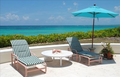 Oceanfront patio with 4 chaise lounges and round table with 4 chairs