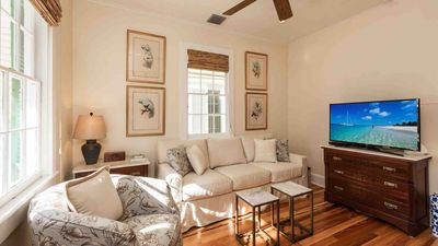 The living room has comfortable seating, and a large flat screen TV...
